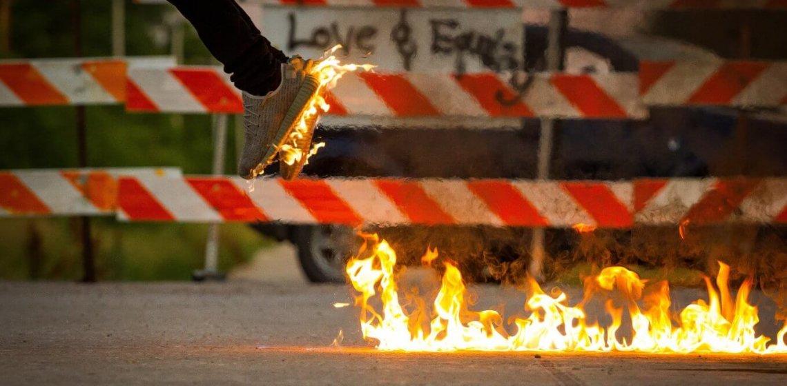 Symbolbild für Wirkung des Mittagsschlafs: Mann springt mit brennendem Schuh von Straße ab, auf der Flammen flackern