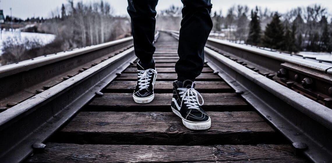 Junger Mann läuft Bahntrasse entlang
