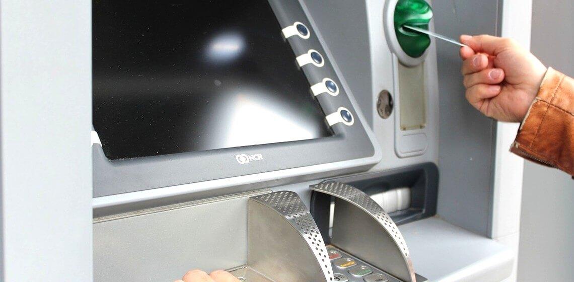 Mann schiebt Kreditkarte in Geldautomat