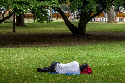 Mann schläft in einem Park auf der Wiese