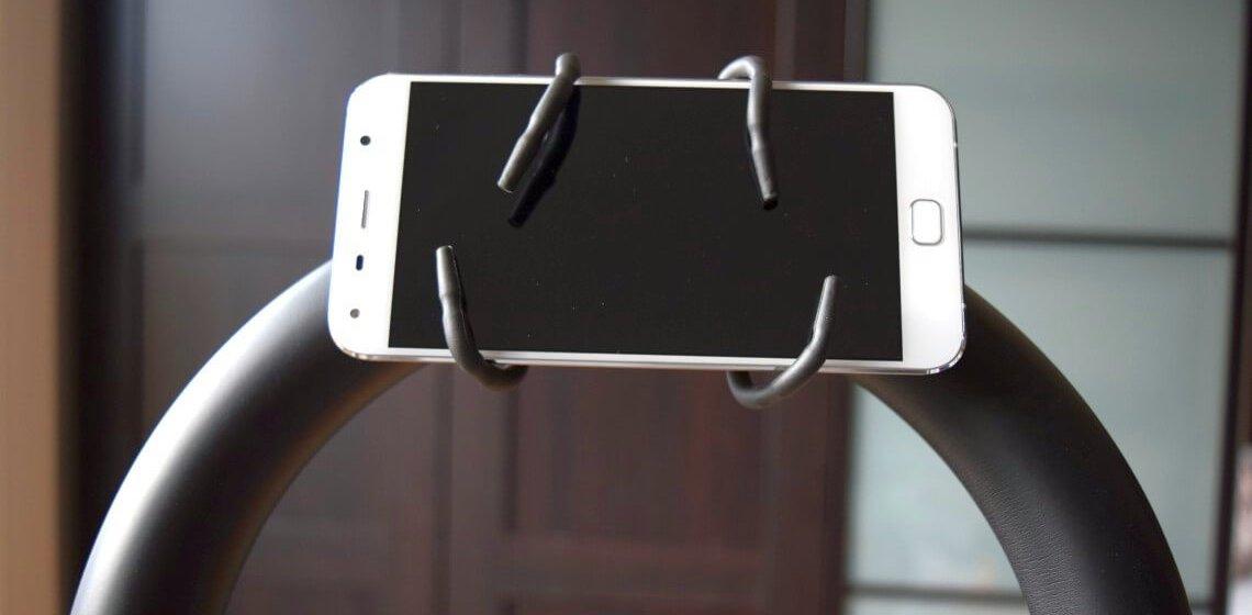 Smartphone-Halterung umklammert Smartphone an gebogener Crosstrainer-Haltestange