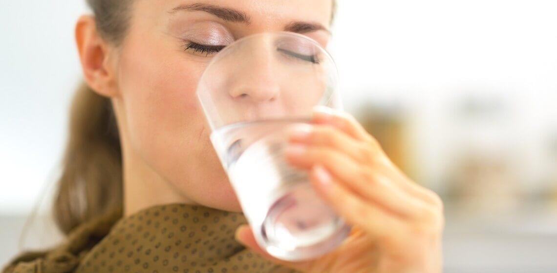 Frau trinkt Leitungswasser aus Glas