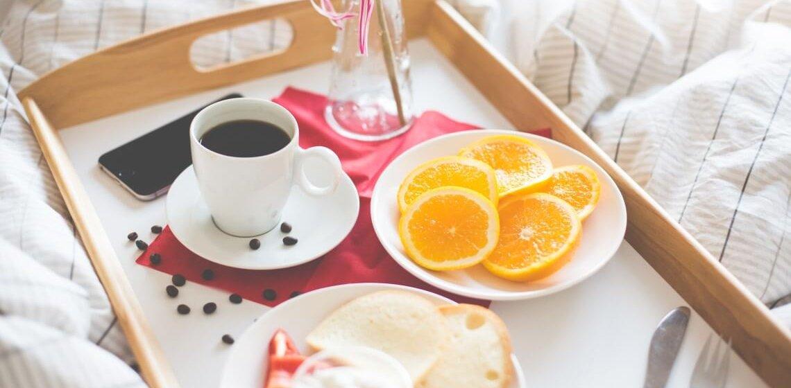 Tablett mit Genießer-Frühstück auf Bettdecke