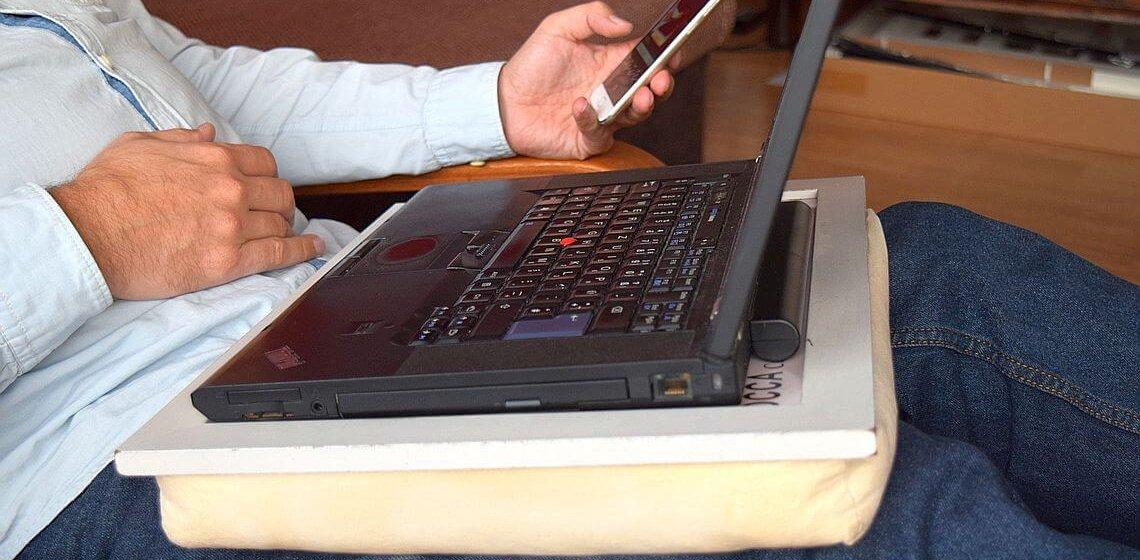 Knietablett mit Laptop steht auf einem Schoß