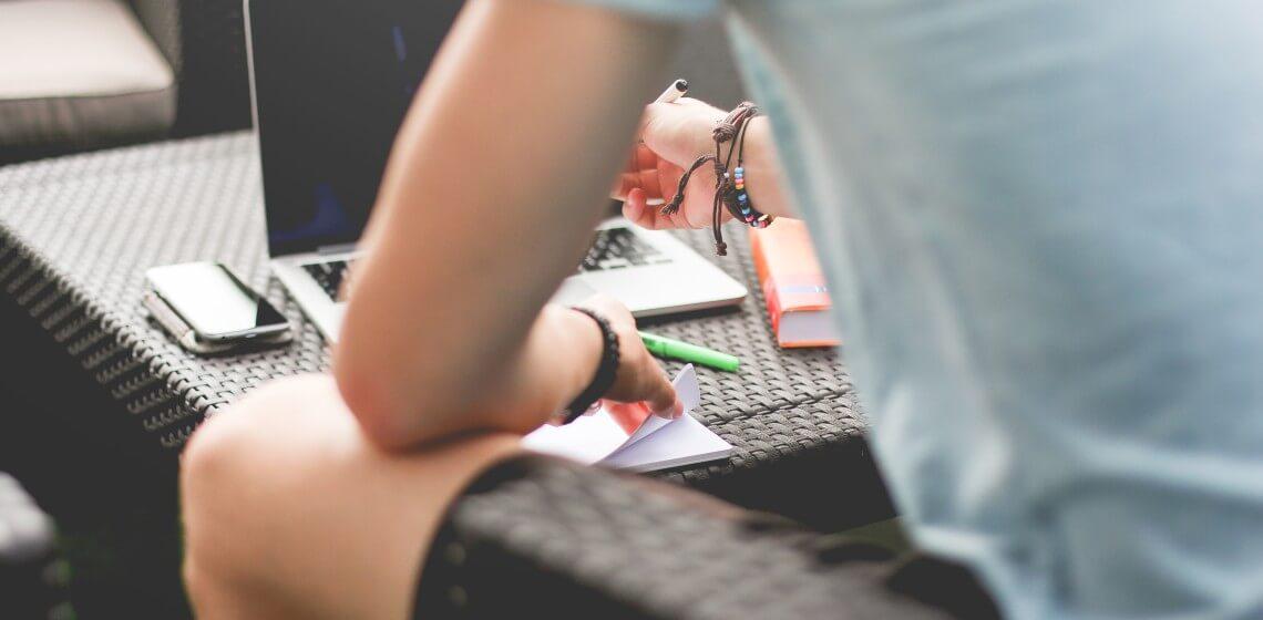Junger Mann arbeitet an Gartenmöbeln sitzend mit Notebook und Buch am Fernstudium