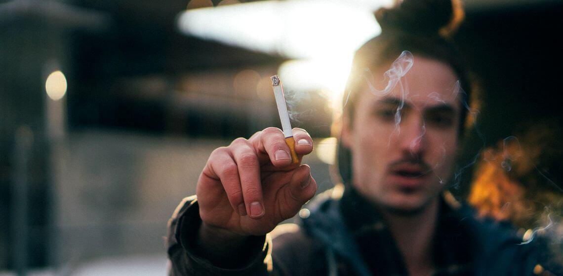 Rauchen aufhören? Raucher mit brennender Zigarette in der Hand