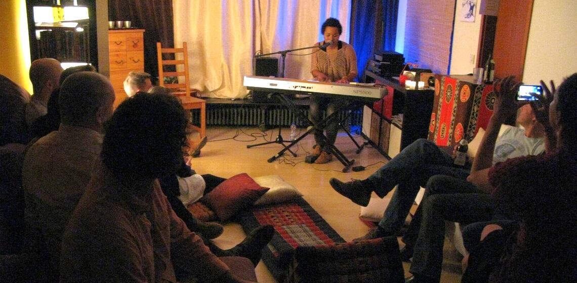 Publikum lauscht Musikerin am E-Piano bei Wohnzimmerkonzert