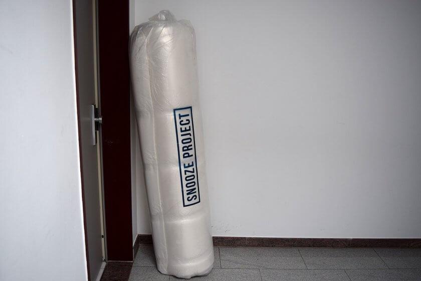 Eingerollt verpackte Matratze mit Verpackungsaufschrift Snooze Matratze lehnt neben Wohnungstüre