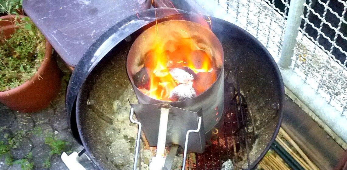 Blick von oben in Anzündkamin mit glühender Kohle umgeben von Flammen
